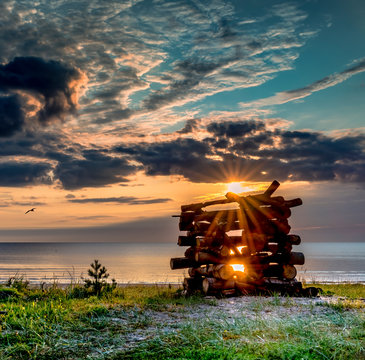 Coastal landscape on a beach of the Baltic beach in Jurmala, Latvia, Wooden log deck for a fire that will be used as a symbol of traditional Latvian holiday of summer solstice - Ligo