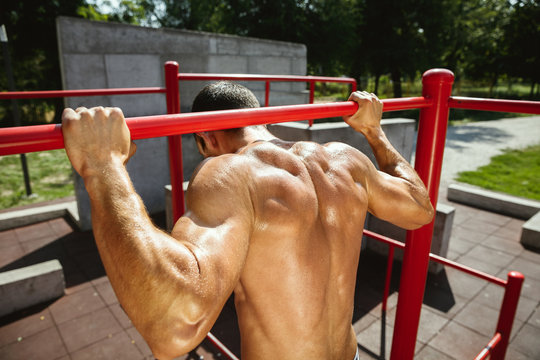 Young muscular shirtless caucasian man doing pull-ups on horizontal bar at playground in sunny summer's day. Training his upper body outdoors. Concept of sport, workout, healthy lifestyle, wellbeing.