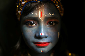 A child dressed as Hindu Lord Krishna poses during the festival of Janmashtami, marking the birth of Hindu Lord Krishna, in Dhaka