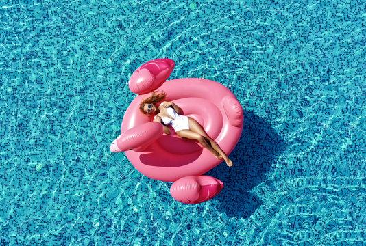Beautiful  sexy woman inflatable giant pink flamingo float mattress in blue swimming pool with text space. Summer vibes tourist