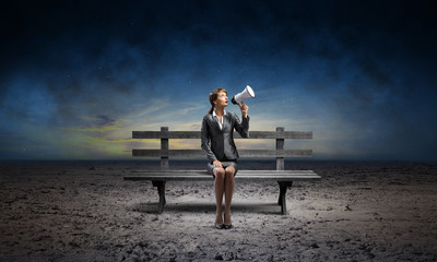 Business woman with megaphone on wooden bench