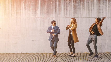 Cheerful Girl and Happy Young Man with Long Hair are Actively Dancing on a Street. Businessman in a Suit Joins Them. They Wear Brown Leather Jacket and Coat. Sunny Day.