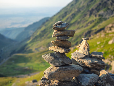 Stone stack with balanced stones on blurred mountain background in sunset warm light