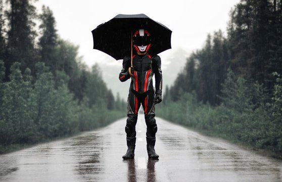 Motorcyclist in full gear and helmet with umbrella in the rain. Motorcyclist in the dark woods
