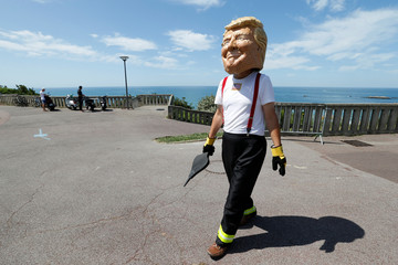 An Oxfam activist wearing giant papier mache head depicting G7 leader U.S. President Donald Trump poses dressed as firemen to draw attention to fighting inequality, on the eve of the G7 summit in Biarritz