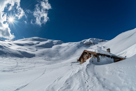 winter chalet in the mountains sun, snow in the Alps