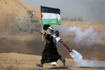 Woman holding a Palestinian flag runs as tear gas fired by Israeli forces during an-anti Israel protest in the southern Gaza Strip
