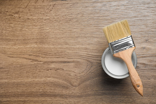 Open can with white paint and brush on wooden background, top view. Space for text