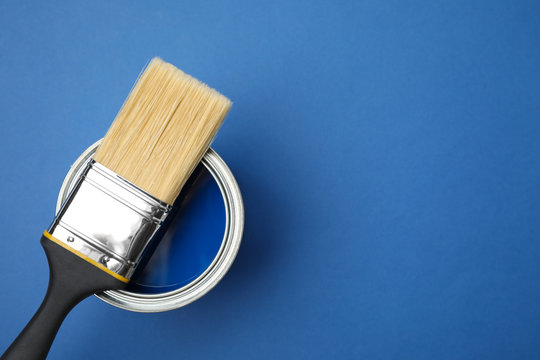 Open can with paint and brush on blue background, top view. Space for text