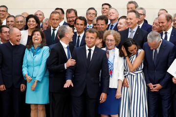 French President Emmanuel Macron poses for a family picture after holding consultative talks ahead of the Biarritz G7 summit, at the Elysee Palace in Paris