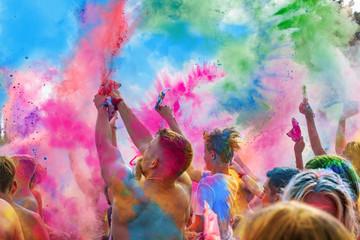 Holi Fest begeisterte Menschen jubeln auf einem Holifestival, tanzen und werfen mit buntem Holipulver