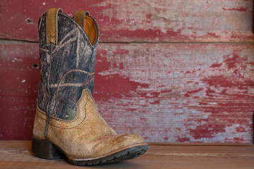 camouflage cowboy boots with red barn board background