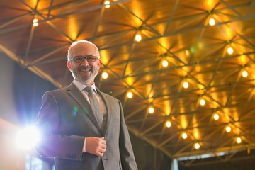 Low angle view of senior businessman in suit wearing eyeglasses standing against illuminated roof Wall mural