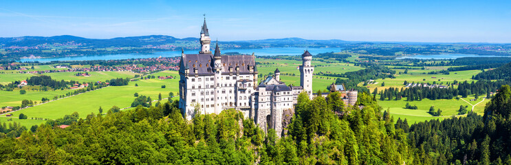 Fototapete - Neuschwanstein castle in Munich vicinity, Bavaria, Germany. This fairytale castle is a famous landmark of Germany. Landscape with mountains and Neuschwanstein castle. Scenic panoramic view in summer.