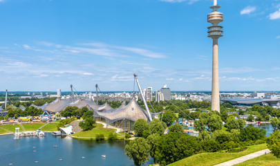 Fototapete - Munich Olympiapark in summer, Germany. It is the Olympic Park, landmark of Munich. Scenic view of former sport area from above. Cityscape of Munich with communication tower. Skyline of Munich city.