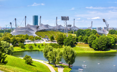 Fototapete - Munich Olympiapark in summer, Germany. Scenic view of Olympic stadium and lake. Panorama of the famous Munich sport area. Cityscape of Munich with beautiful park. Landscape of green European city.