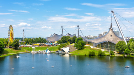 Munich Olympiapark in summer, Germany. It is the Olympic Park, landmark of Munich. Scenic view of former sport area. Panorama of the green Munich district with lake. Beautiful skyline of Munich city.