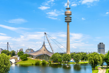 Munich Olympiapark in summer, Germany. It is the Olympic Park, landmark of Munich. Scenic view of former sport district. Scenery of Munich with tower and lake. Beautiful landscape of Munich city.