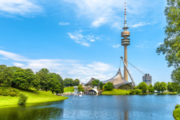 Wall Mural - Munich Olympiapark in summer, Germany. It is the Olympic Park, landmark of Munich. Scenic view of former sport district. Scenery of Munich with tower and lake. Beautiful landscape of Munich city.