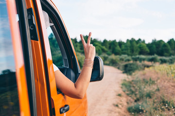 attractive blonde girl taking off arm in car window with v on fingers