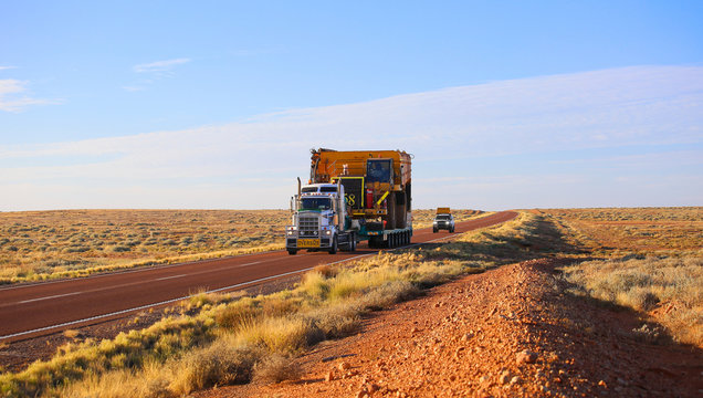 """Truck oversize rides on road. Large truck driven mining dumper. Oversized blocked all way. """"Oversize"""" wide load"""