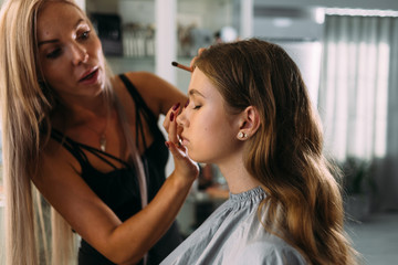 professional expert, make up stylist, makes up a young beautiful girl, photo shoot for the magazine