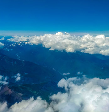 Mount Ranier in Distance beyond clouds from above