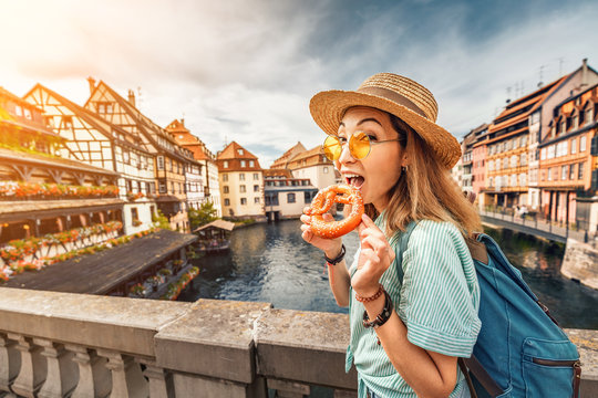 Happy asian girl tourist eating delicious pretzel while travelling in Europe. Tourism and food concept