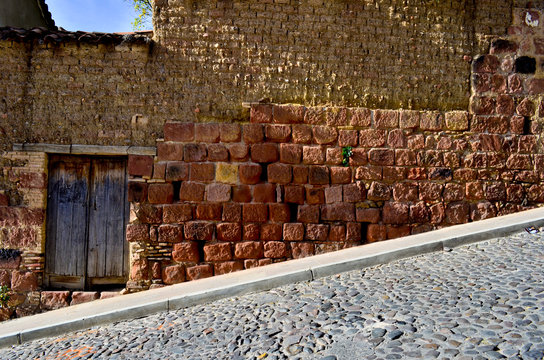 Street downhill with red brick facade with a door, in Sucre, Bolivia