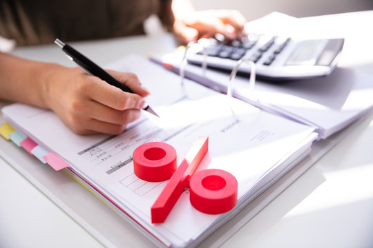 Businessperson's Hand Calculating Bill With Calculator