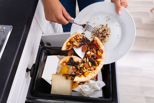 Person Throwing Pepperoni Pizza In Dustbin