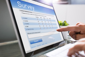 Man Giving Online Survey On Laptop