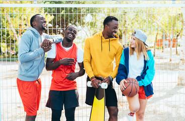 Multiethnic teenager group having fun playing basketball
