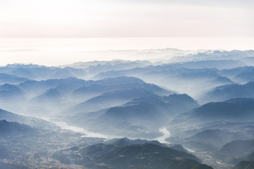 Landscape aerial view of colorful blue Alps mountains with clouds, rivers, and fog above Switzerland