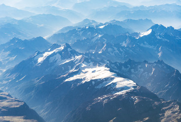Landscape aerial view of colorful blue Alps mountains with clouds and fog above Switzerland