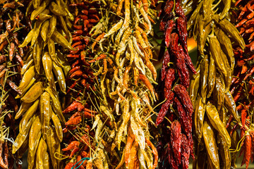Variety of yellow, orange, and red dried chili peppers at the farmers market stall