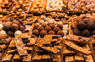 A large selection of different chocolate types, chocolate truffles, and other sweets with chocolate at the farmers market stall
