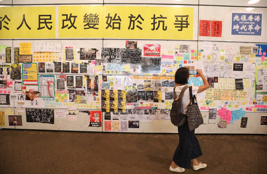 """A woman takes a photo as she passes a """"Lennon Wall"""" filled with posters and post-it notes at Tung Chung station, in Hong Kong, China"""