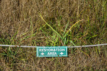 Natural grassland restoration green and white information sign with rope on ground.