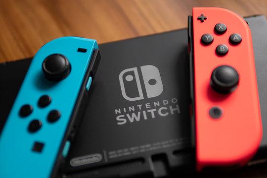 Bangkok, Thailand - July 27, 2018 : Joy-Con, the Nintendo Switch controller, was placed beside the Nintendo Switch Logo.