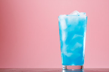 Glass of a blue alcoholic cocktail drink with ice. Blue long drink cocktail alcoholic non-alcoholic cold beverage drink.