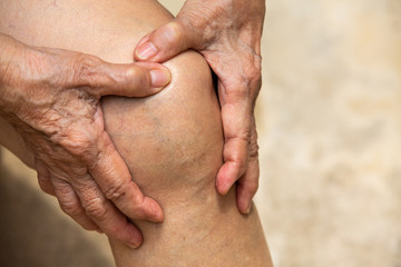 Senior woman suffering from knee pain sitting on chair, Massaging by her hand, Close up, Body concept Fototapete