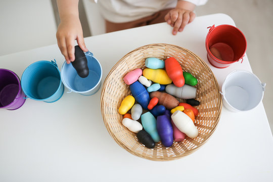 toddler sorts colorful toys by colored buckets