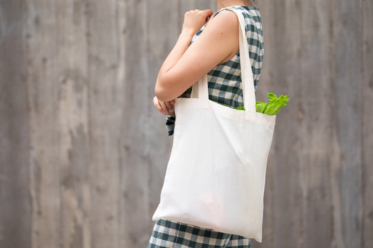 Female hand with cotton eco bag on wooden grey background. Zero waste concept