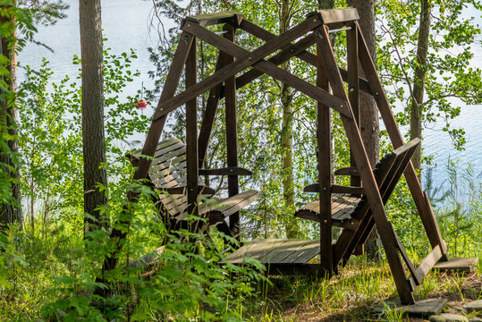 A wooden swing on the shores of the Saimaa lake in Finland