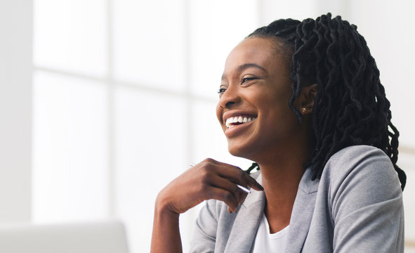 Portrait Of Black Office Girl Laughing Sitting Against Window