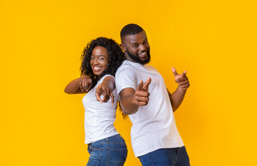 Joyful young black couple pointing fingers at camera
