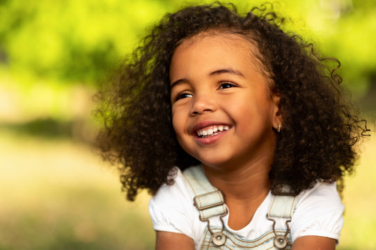 Cute afro girl smiling broadly outdoors, having picnic with parents