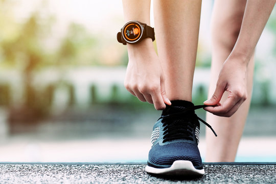 A girl using smart watch for tracking running