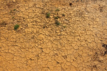 Aerial view of Cracked Clay surface in dry desert environment after drought, with natural pattern and texture as background and copy space